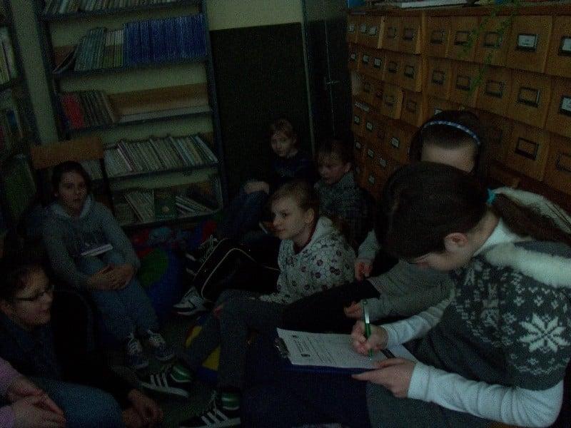 """Wnętrze biblioteki. Grupa dzieci z DKK SP nr3 wspólnie omawiają książkę Barbary Kosmowskiej """"Buba"""" i """"Buba.Sezon ogórkowy""""."""