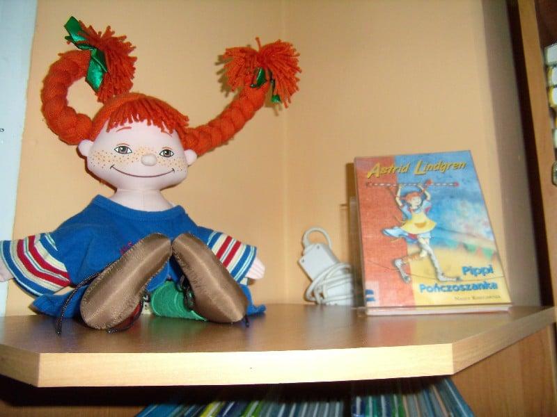 Na stoliku leży maskotka lalka pipilangstrumpf oraz książka Astrid Lindgren Pippi Pończoszanka.