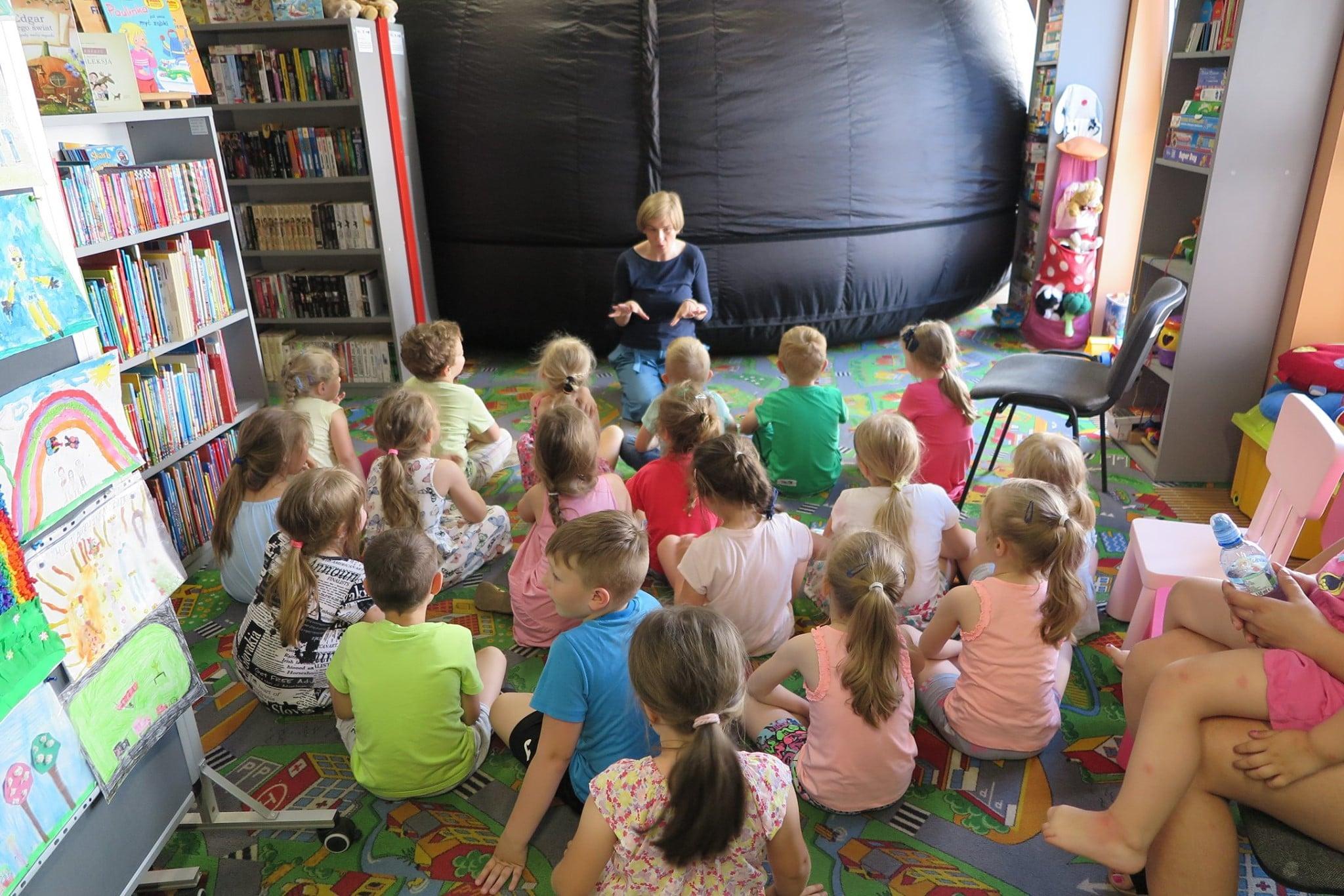 Wnętrze biblioteki.  W grupie siedzą dzieci, w tle mobilne planetarium.