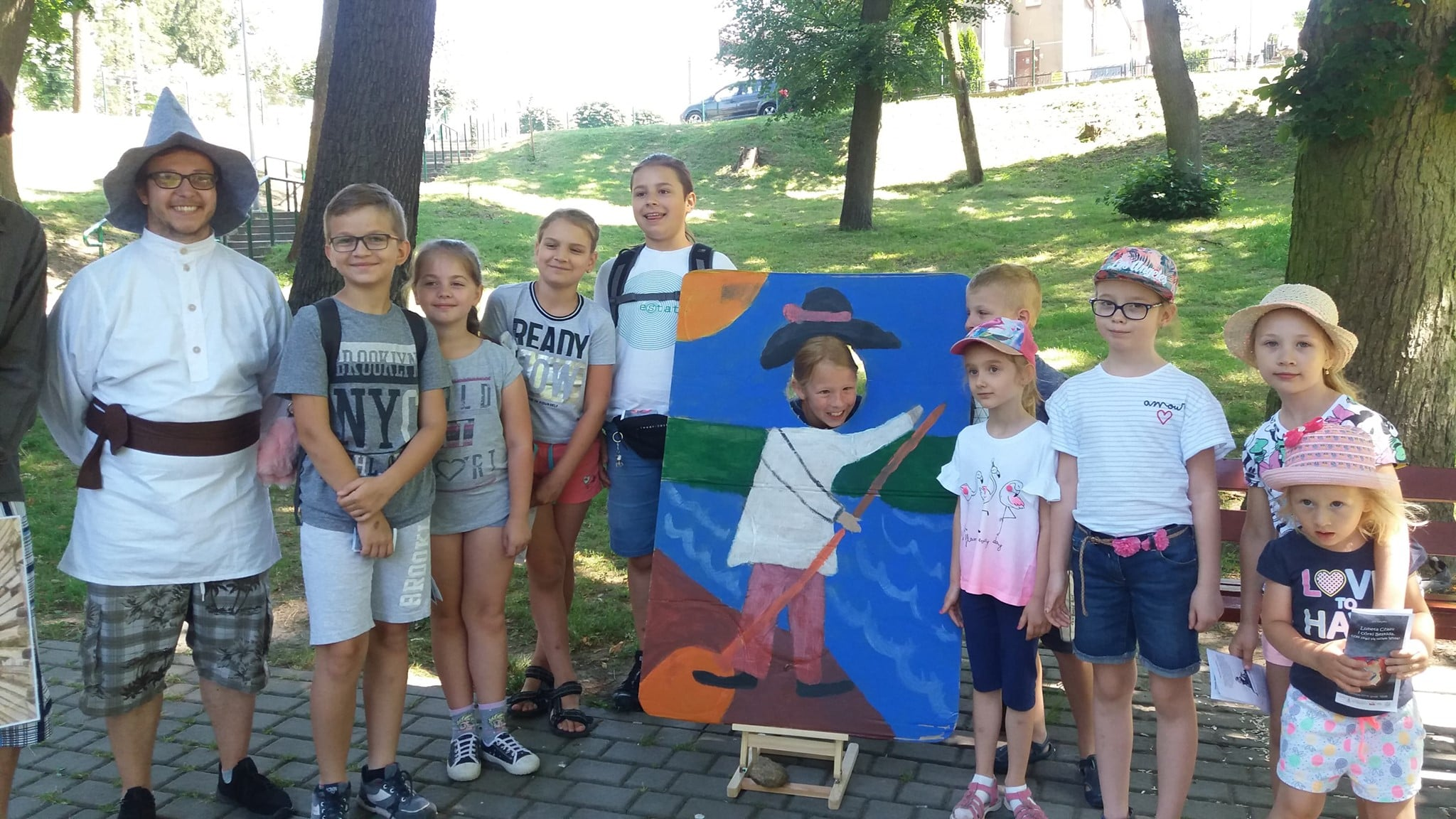 """Wnętrze parku. Grupa dzieci biorąca udział w grze miejskiej pt. """"Luneta Czasu i córki Beskida, czyli skąd się wzięła Wisła?''."""