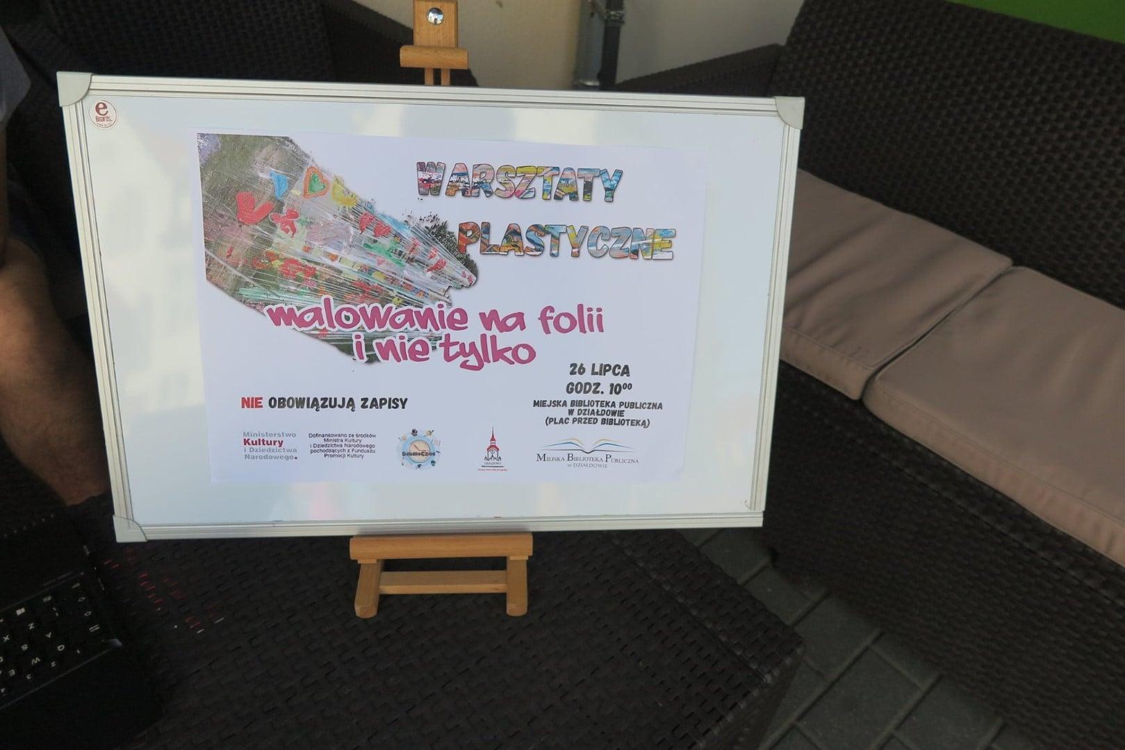 Na sztaludze plakat MBP ''Warsztaty Plastyczne''. Malowanie na folii i nie tylko. 26 lipca godz.10:00.