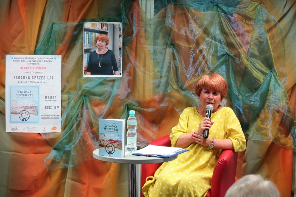 Na czerwonym fotelu siedzi autorka książki ''Zagadka sprzed lat'' Elżbieta Zakrzewska.