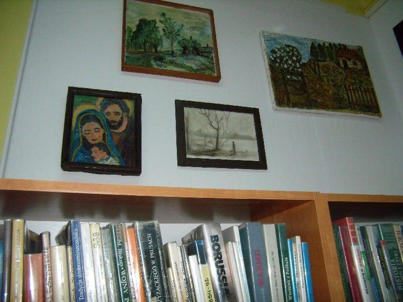 W bibliotece na ścianie wisi wystawa obrazów Bernarda Żóralskiego.
