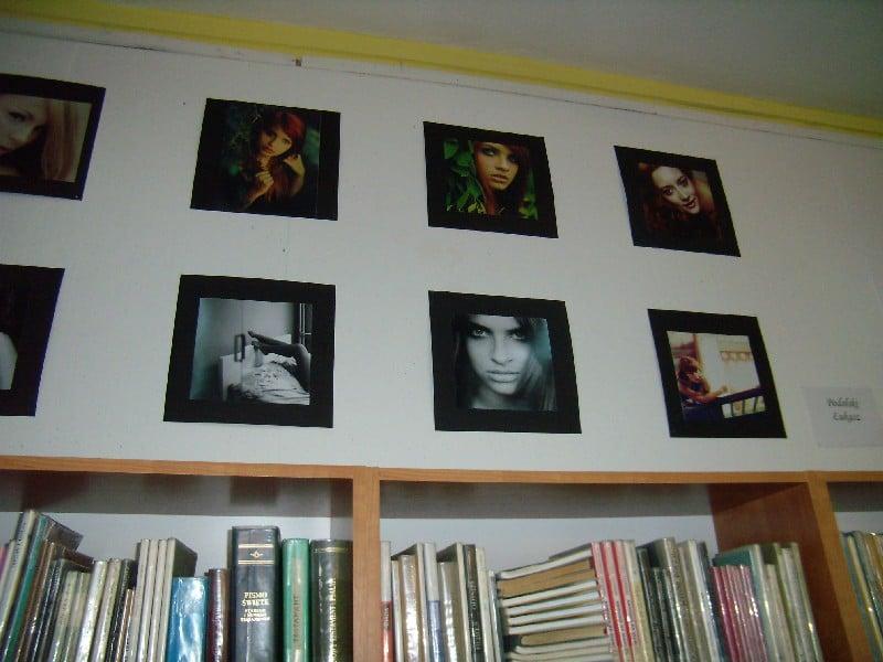 Na ścianie w bibliotece wisi wystawa zdjęć Łukasza Podolskiego.