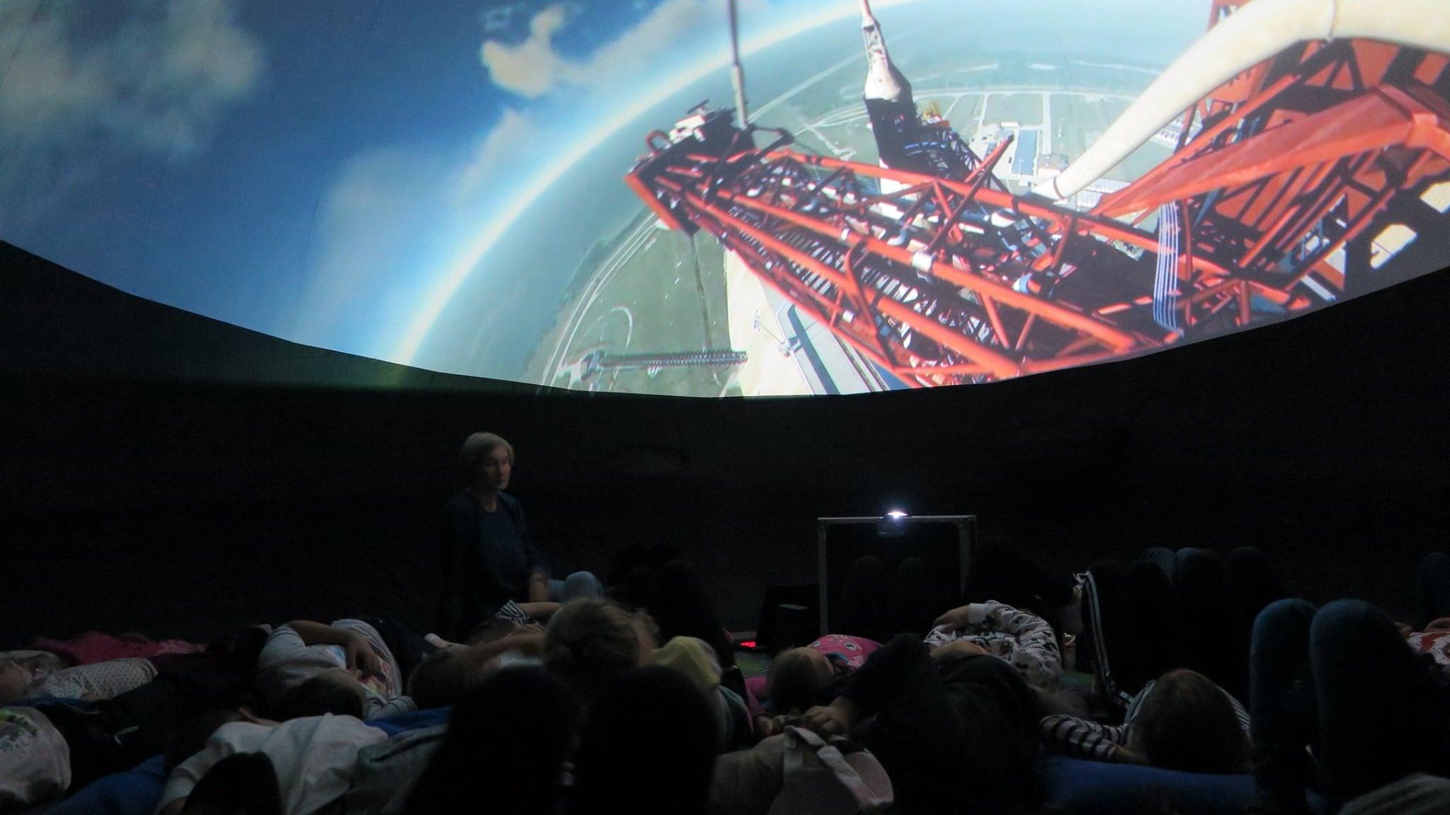 Grupa dzieci ogląda mobilne planetarium,historię podboju księżyca, tajemnice układu słonecznego oraz historię lotów kosmicznych.