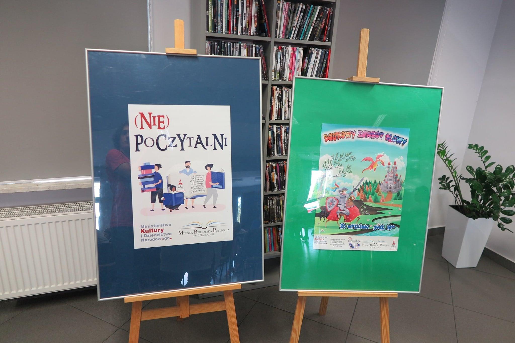 Dwie sztalugi z plakatami. Na sztaludze z niebieskim tłem plakat (Nie) poczytalni, na sztaludze z  zielonym tłem plakat Bajkowy Zawrót Głowy.