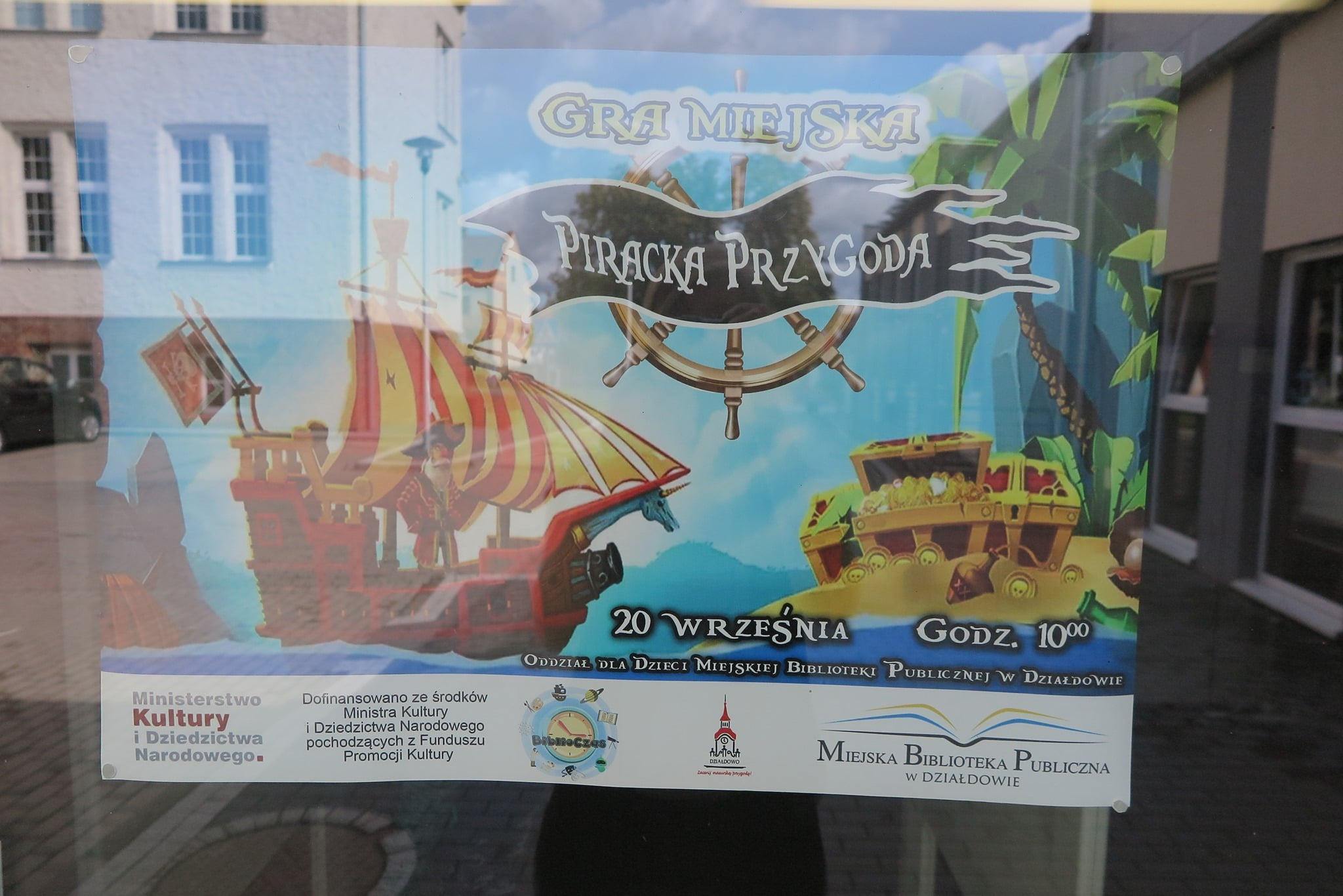Na szybie plakat z napisem ''Gra Miejska Piracka Przygoda'', na plakacie piracki statek, i skarb piratów.