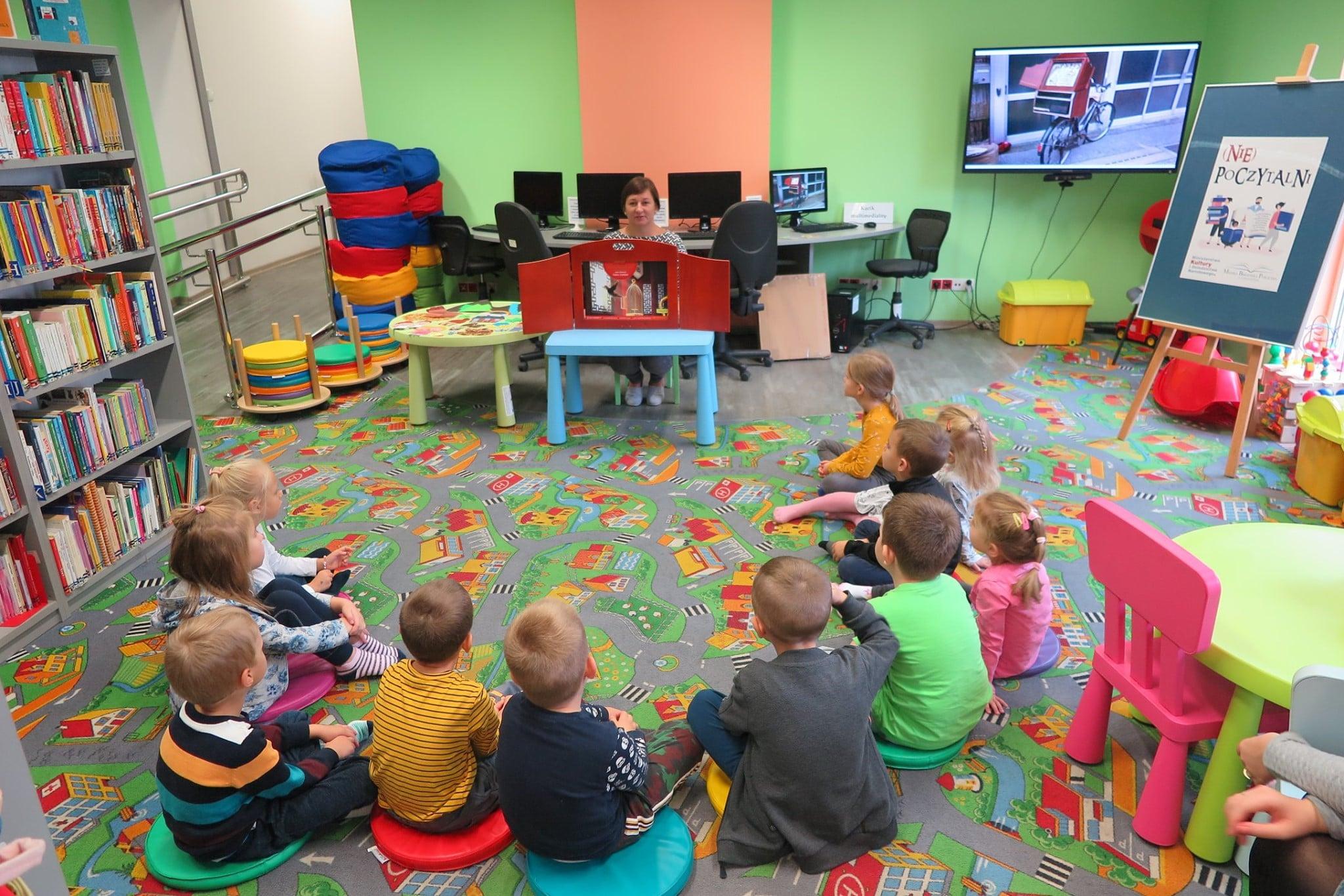 Wnętrze biblioteki ,oddział dla dzieci. Dzieci siedzą na pufach i słuchają teatrzyku kamishibai, który czyta bibliotekarka Ania Wiśniewska.