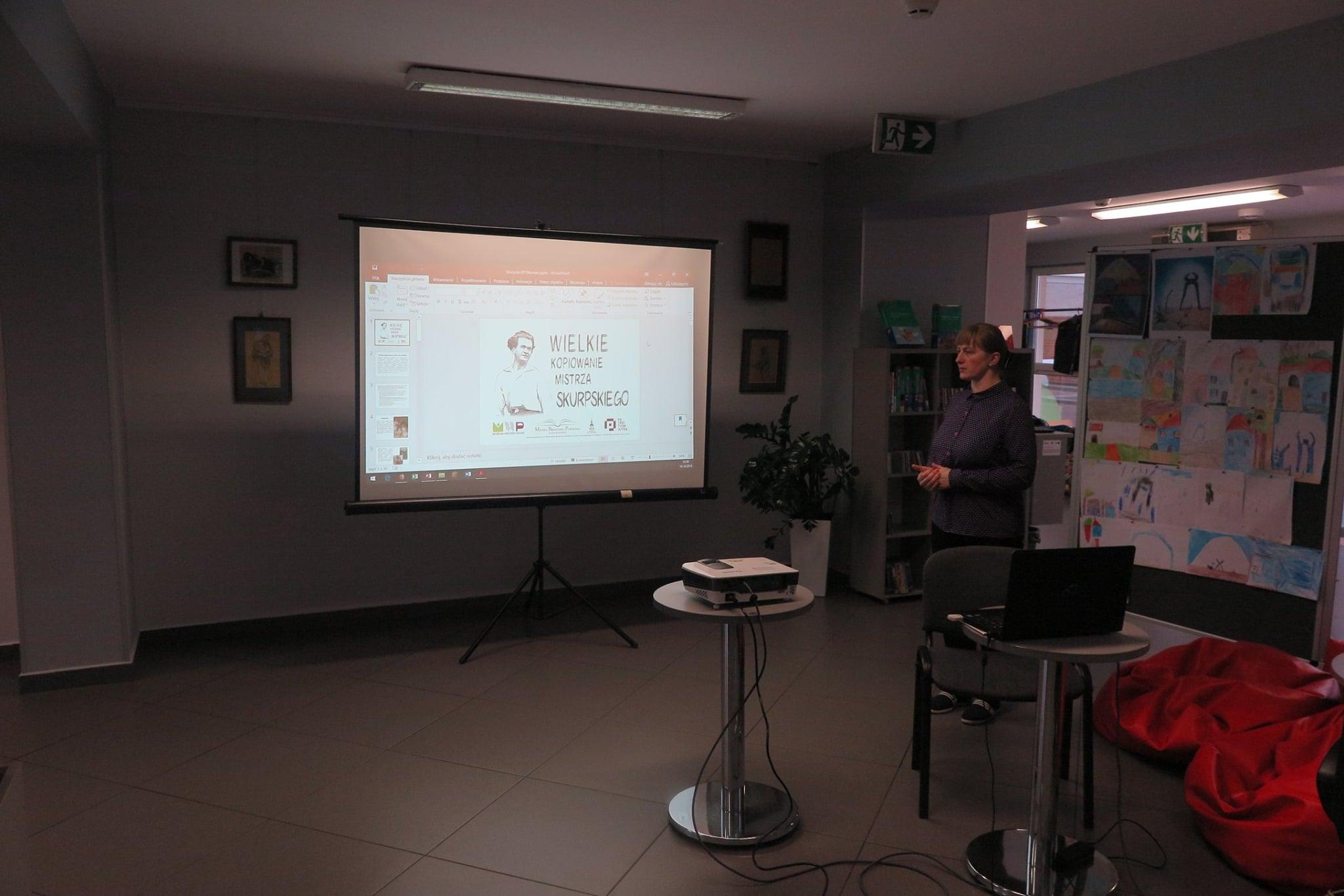 Wnętrze biblioteki,mediateka. Bibliotekarka Małgorzata Trąmpczyńska prowadzi warsztaty w ramach projektu ,,Wielkie kopiowanie mistrza Skurpskiego''. W tle na monitorze plakat Wielkie kopiowanie mistrza Skurpskiego''.