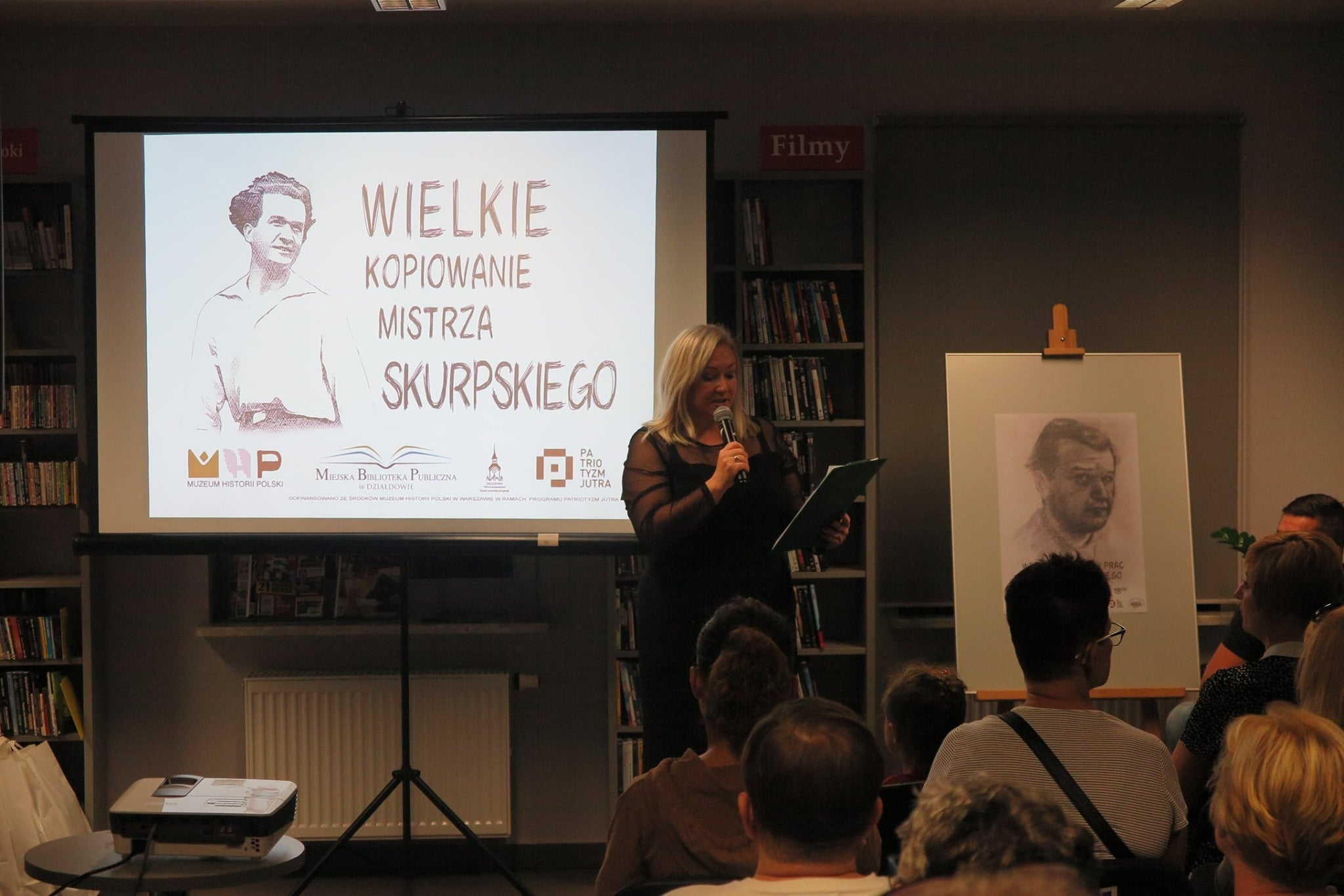 Wnętrze biblioteki,mediateka. Dyrektor MBP wita przybyłych gości z okazji wernisażu wystawy prac Hieronima Skurpskiego. W tle monitor z napisem ''Wielkie kopiowanie mistrza Skurpskiego.