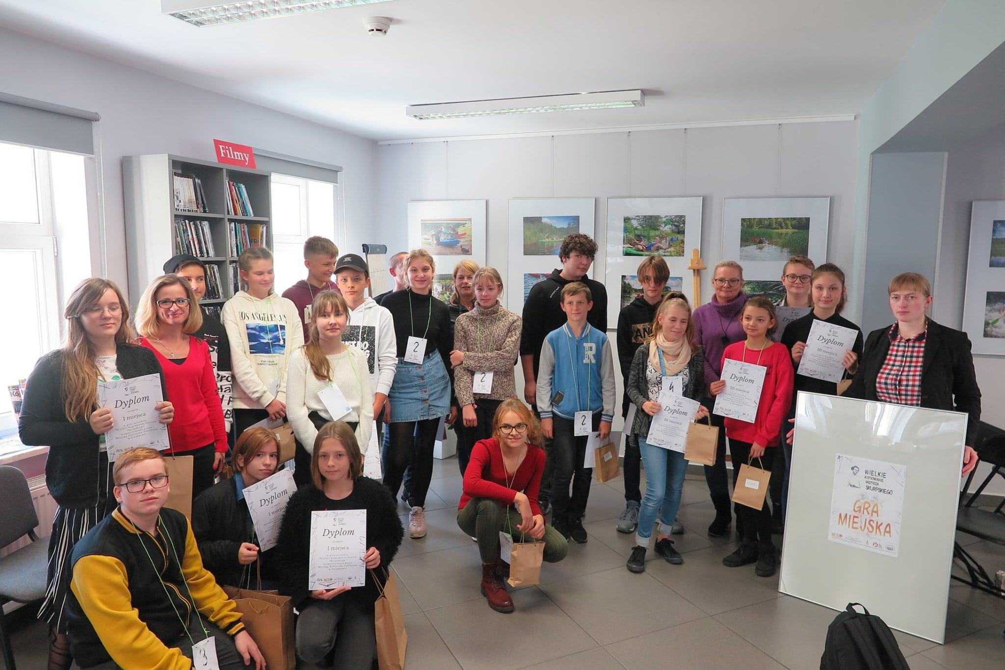 Wnętrze biblioteki,mediateka. Uczniowie SP nr 2 z dyplomami za udział w grze miejskiej wraz z bibliotekarką Małgorzatą Trąmpczyńską.