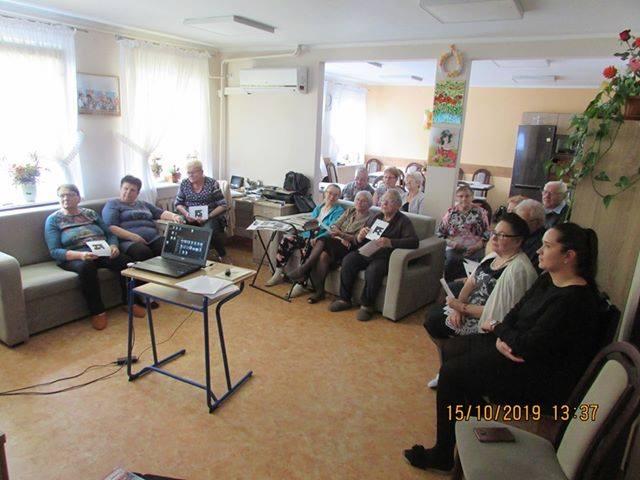 Wnętrze dom seniora ,,Wigor'' na kanapach siedzą seniorzy słuchają wykładu w ramach projektu ,,Wielkie kopiowanie mistrza Skurpskiego''.
