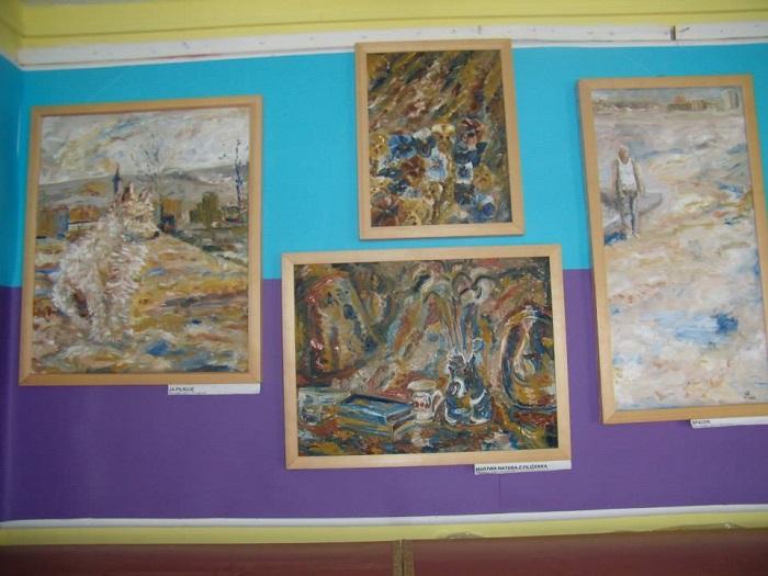 Wnętrze biblioteki, na ścianie wisi wystawa malarstwa Jana Chądzyńskiego z Mławy.