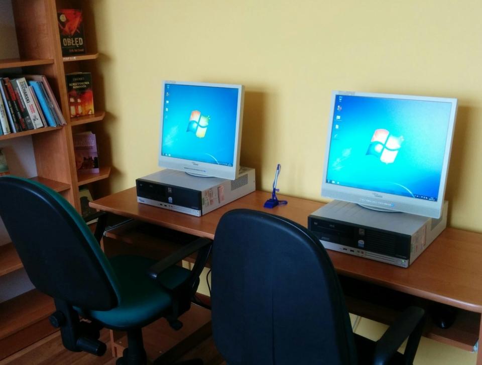dwa komputery stacjonarne z monitorami na stole pod ścianą z dwoma fotalami przed nim
