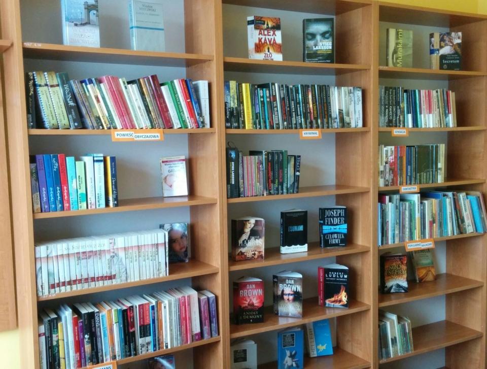 trzy regały z książkami w pomieszczeniu filii bibliotecznej