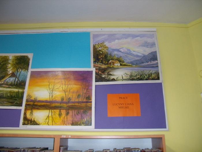 Wnętrze biblioteki na ścianie wisi wystawa krajobrazów Lucyny i Jana Mielke.