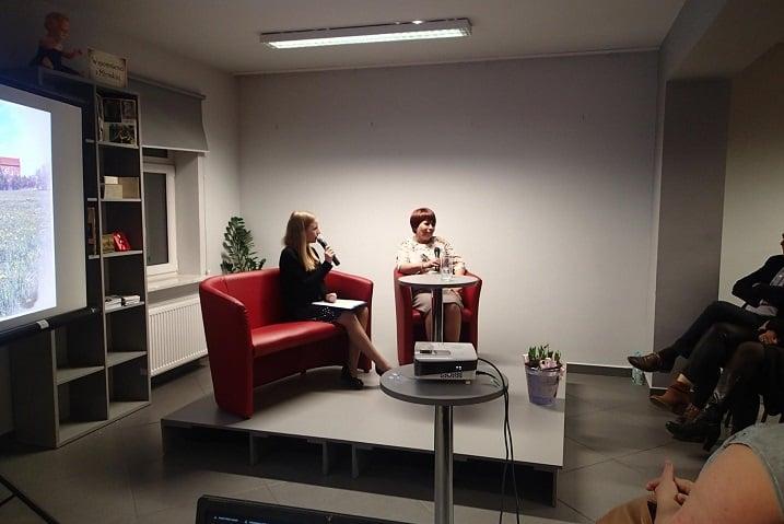 """Wnętrze biblioteki,mediateka. Przy stoliku autorka  książki """"Moja Młyńska"""", Elżbieta Zakrzewska."""
