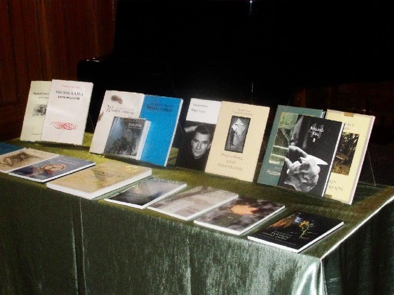 Na stoliku leżą książki różnych poetów z okazji  IV Ogólnopolskiego Konkursu Poetyckiego.