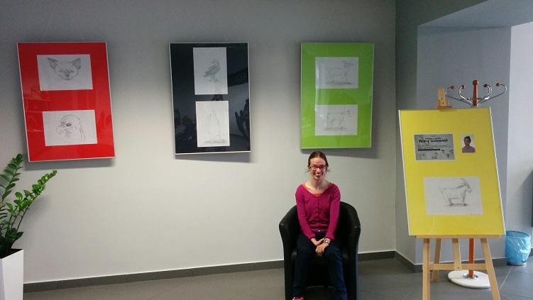 Na ścianie wisi wystawa rysunków, na fotelu siedzi ich autorka Anna Wdowiak.