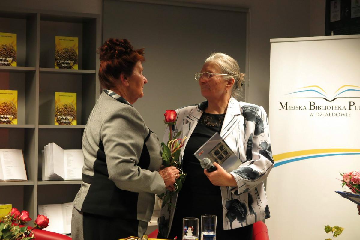 Wnętrze biblioteki,mediateka. Przy tablicy MBP w Działdowie Anna Kazimiera Cegiełka otrzymuje czerwoną różę od czytelniczki.