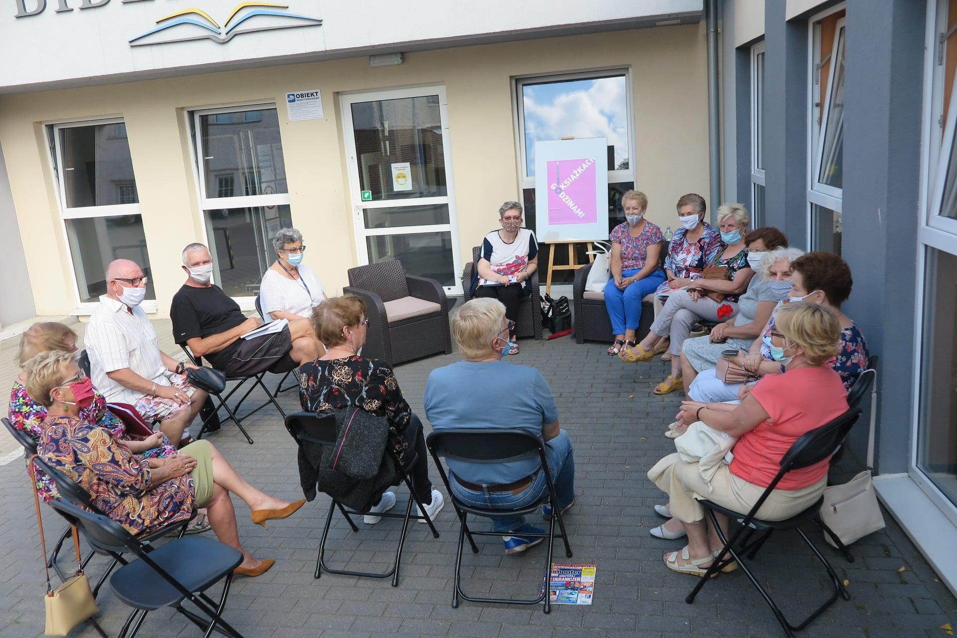 Przed budynkiem MBP w Działdowie 15 osób z DKK Uniwersytetu Trzeciego Wieku w Działdowie prowadzi dyskusje na temat książki ,,Zawsze ktoś patrzy'' Joya Fielding.
