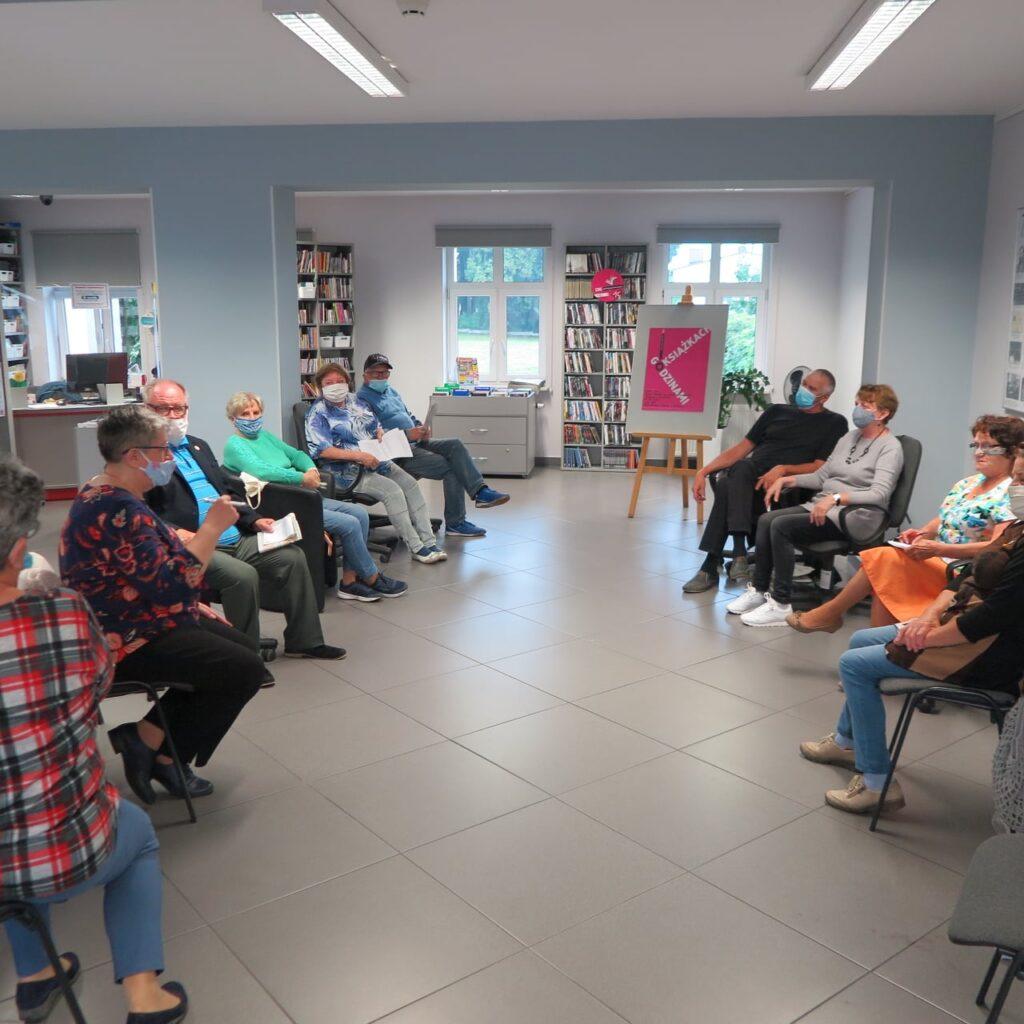 Wnętrze biblioteki. Spotkanie Dyskusyjnego Klubu Książki.10 osób siedzi na krzesłach. W tle sztaluga ,,Godzinami o książkach''.