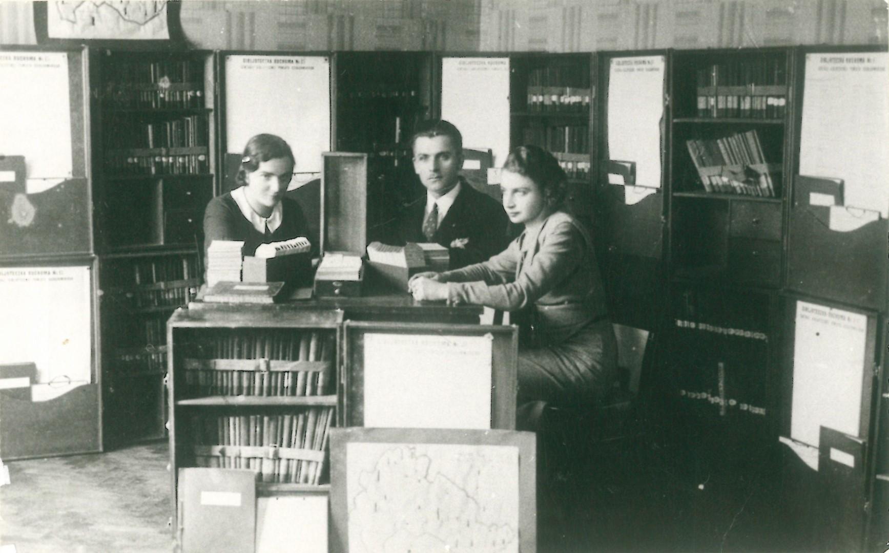Organizatorzy Powiatowej Centrali Bibliotek Ruchonych Piotr Pszenny, Benigna Gapińska, Janina Czajkowska. Na zdjęciu widzoczne są szafki-walizki, w których książki wysyłano w teren