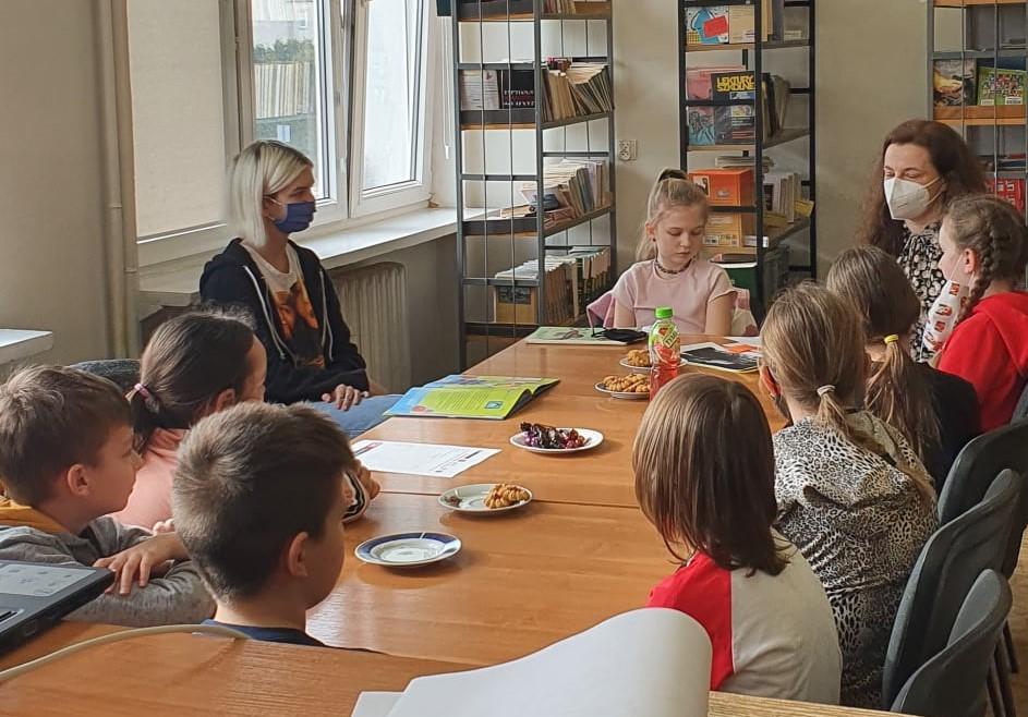 dzieci i nauczyciel prowadzący DKK w szkolnej bibliotece podczas omawiania książki