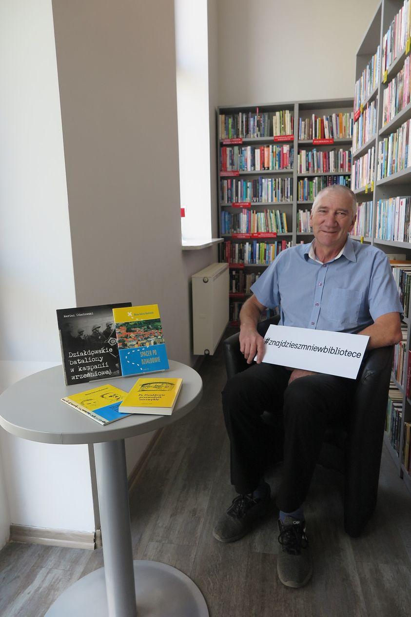 Marian Odachowski w fotelu pośród książek