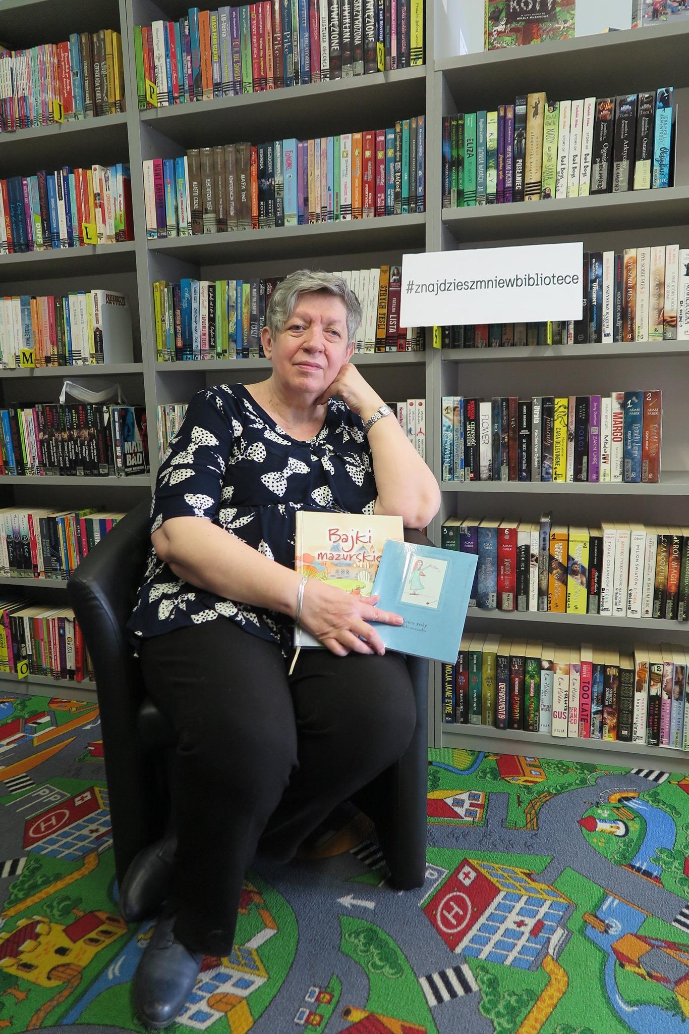 Ewa Sotomska na tle książek w bibliotece
