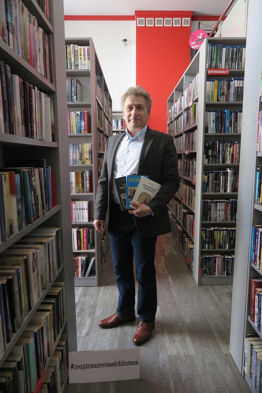 Dariusz Piotrowicz pośród książek w bibliotece