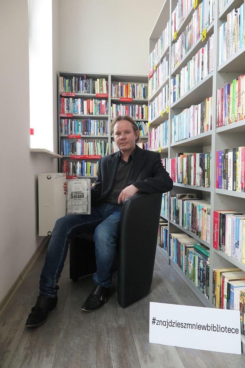 Radosław Wiśniewsk w fotelu pośród księgozbioru biblioteki