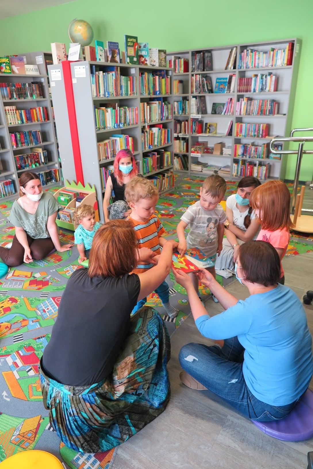 Wnętrze oddziału dla dzieci Miejskiej Biblioteki Publicznej w Działdowie. Bibliotekarka siedząc bokiem na pufie pokazuje małym dzieciom książkę dźwiękowa. Obok niej kuca kobieta, na przeciw nich siedzą trzy Panie i dziecko na pufach, a troje małych dzieci ogląda książkę.