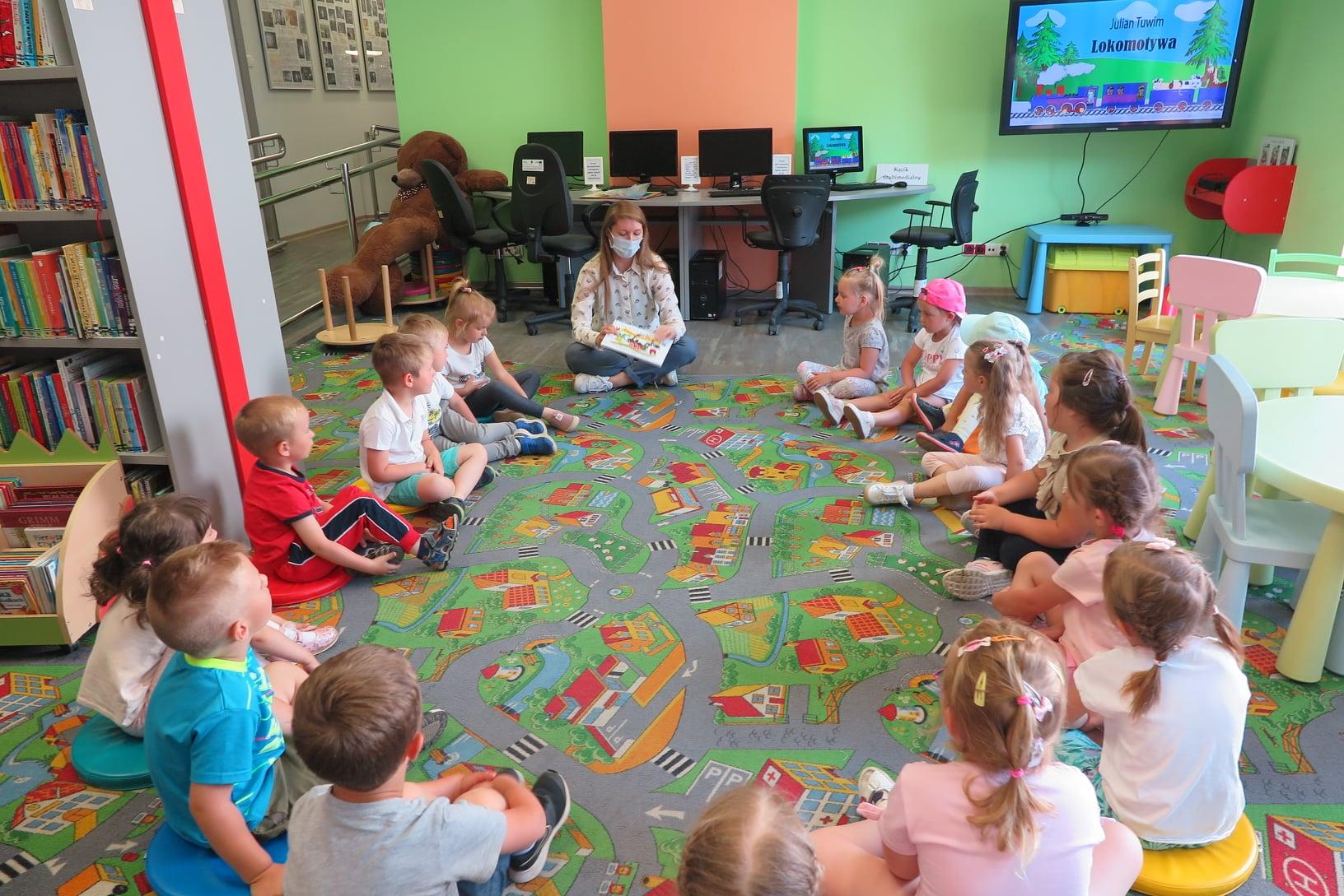 """Na zdjęciu szesnaścioro dzieci i jedna kobieta siedzą w okręgu na podłodze w Oddziale dla dzieci. W tle na telewizorze wyświetlona jest ilustracja pociągu i napis: """"Julian Tuwim. Lokomotywa"""""""